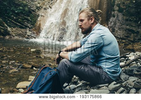 Young Hiker Man With Backpack Sitting On The Rocks Near Waterfall. Trek Hiking Destination Experience Lifestyle Concept