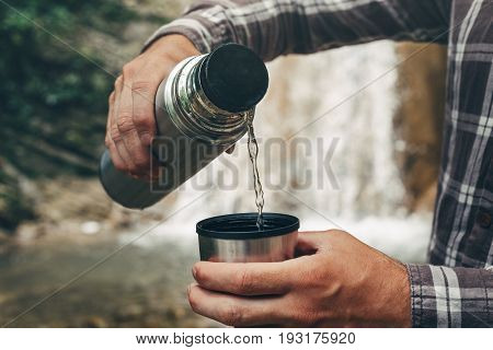 Unrecognizable Traveler Pouring Tea Or Coffee To Cup From Thermos On Waterfall Background. Tourism And Travel Concept
