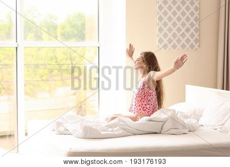 Morning of beautiful young woman sitting on bed at home