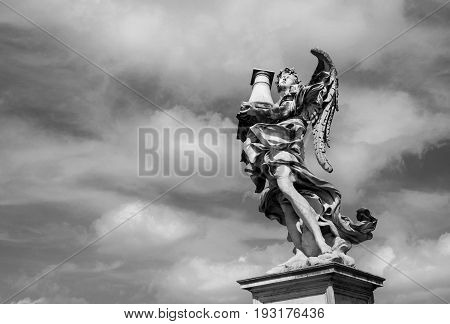Angel statue holding the Holy Column looks at the heavenly sky on Sant'Angelo Bridge in the center of Rome (Black and White)