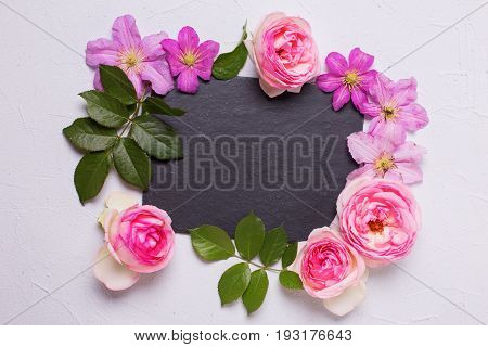 Violet clematis and pink roses flowers and empty slate board on grey textured background. Place for text. Flat lay. Mock up.