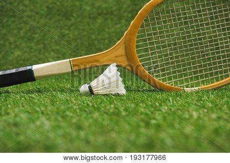 Close Up View Of Badminton Racket And Shuttlecock On Green Lawn