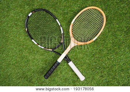 Top View Of Plastic Tennis And Wooden Badminton Rackets On Green Lawn