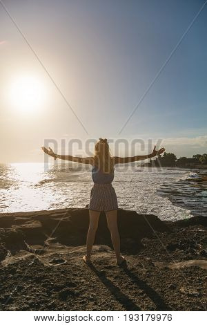 Girl enjoying the ocean with arms wide open.