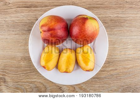 Two Full Nectarines And Pieces Of Nectarine In White Plate