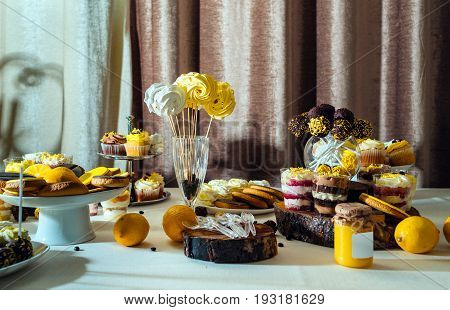 Holiday Candy Bar In Yellow And Brown Color. Wedding Candy Bar Served With Cupcakes, Cake Pops, Bisc
