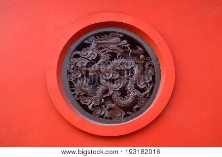 Wooden Carved dragon in circle on red background in Chinese Buddhism Temple in Lumbini, Nepal - birthplace of Buddha Siddhartha Gautama.