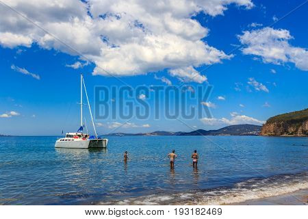 Hinsby beach Tasmania Australia - January 8 2017: beach goers paddling in the shallows near catamaran yacht anchored nearby