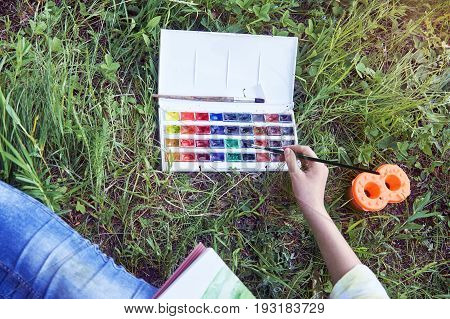 Young female artist's hand dabs a paintbrush into the paints on green grass