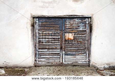 Old wooden gate in grungy white wall. Architecture detail background