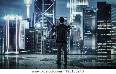 Back view of excited businessman with arms up blurred morden city skyline .
