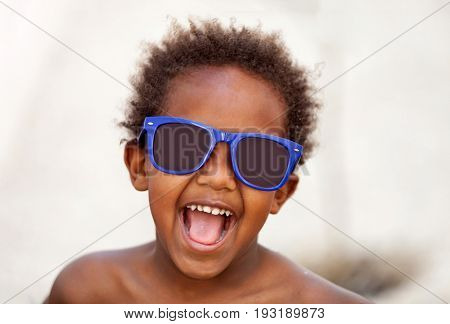 Funny Afro-American kid with blue sunglasses and a beautiful smile
