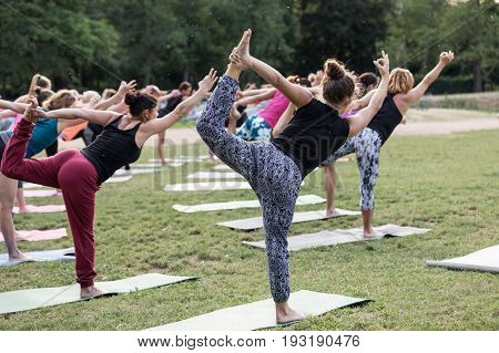 Woman practicing yoga on a meadow. In backround group of women practicing yoga together during a beautiful sunny day on the meadow. Yoga in nature. Concept healthy