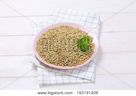 plate of peeled brown lentils on checkered dishtowel