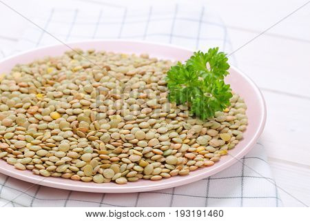 plate of peeled brown lentils on checkered dishtowel - close up