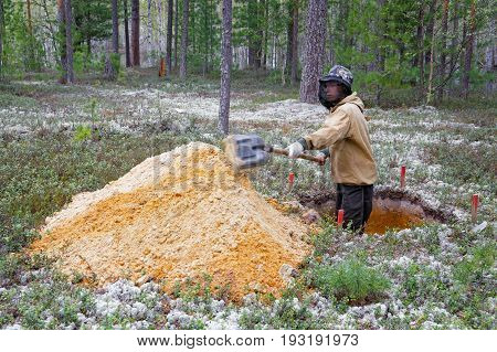 A young archaeologist excavating in the Siberian taiga