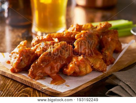 sauced buffalo chicken wings on wooden board with celery