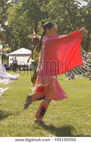 SMITHS FALLS ON JUNE 10 2017 EDITORIAL IMAGE SERIES OF NATIVES POWWOW CEREMONY with this image focused on a young native dancer during the throat singing.