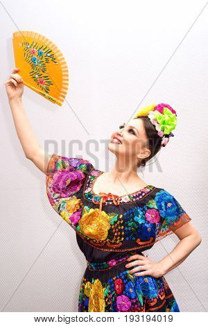 beautiful smiling mexican woman in traditional mexican dress with fan