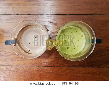 Top view of hot chocolate and green macha tea with froth in glass mug with handles on wooden table