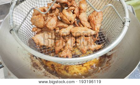 Fried pork in grid basket hanging to drying and zoom in Macro photo focus select at pork around are blur.