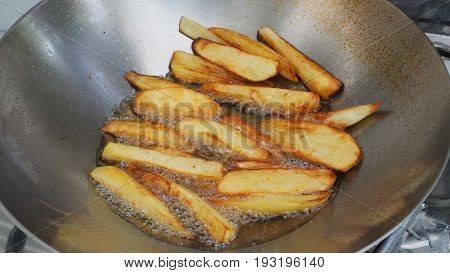 French fries potato snacks cooking with palm oil in stainless steel pan and scorch.