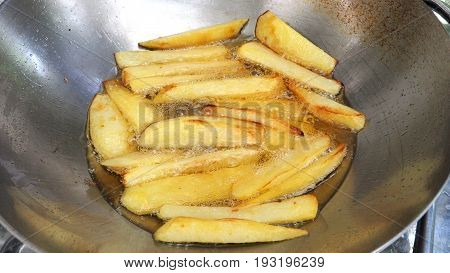 French fries potato snacks cooking with palm oil in stainless steel pan Third step is little scorch to finish.