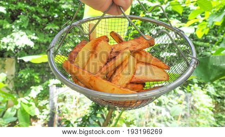 French fries in grid basket My hand to hanging all for take a photo with nature green background at the garden house.