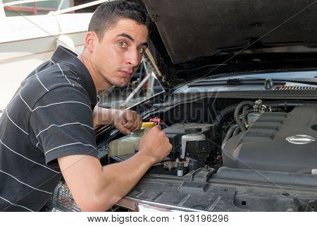 a young man mechanic repairing motor of car