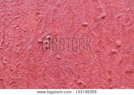 The texture of the walls of wood painted with red paint. Visible cracks bumps and depressions. Under the paint visible old layer of paint.