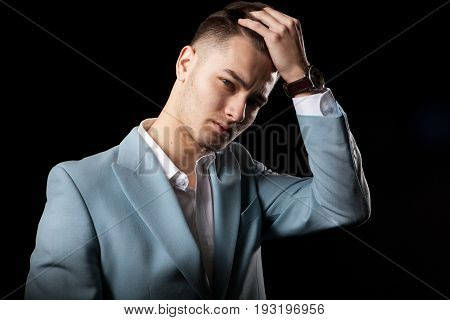 Cool young businessman posing in studio on black background. Confident CEO. Modern fashion corporate worked