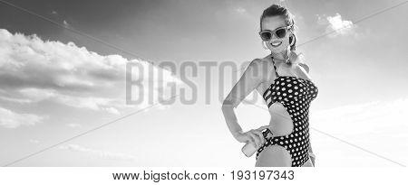 Happy Active Woman In Beachwear On Beach Applying Suntan Lotion