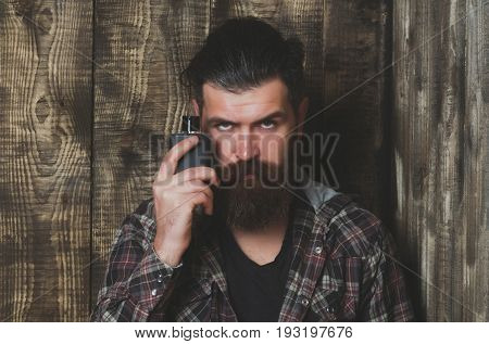 Bearded man or brutal caucasian hipster with grey hair long beard and moustache posing with black perfume or cologne bottle on wooden background. Male fragrance and perfumery. Cosmetics