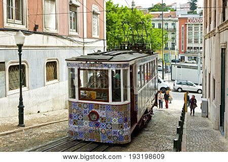 LISBON PORTUGAL - JUNE 11 2013: The Gloria Funicular (Ascensor da Gloria) funicular railway line in Lisbon. Connects Pombaline downtown with the Bairro Alto. Carriage decorated with Azulejos tiles