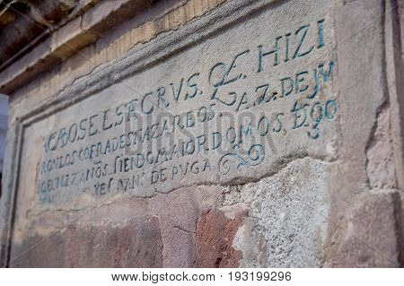 QUITO, ECUADOR - NOVEMBER 23, 2016: Description over a stoned wall in outside of historic Plaza de Santo Domingo in old town Quito Ecuador South America.