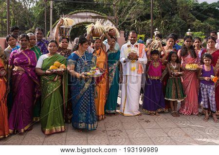 Mysore India - October 27 2013: The white clothed groom is surrounded by group of women in colorful saris during wedding procession. Women carry fruit and palm seed strings as fertility symbols.