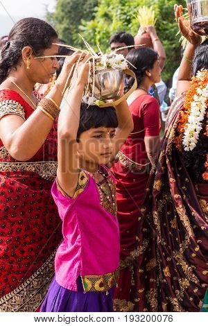 Mysore India - October 27 2013: Closeup of young girl during wedding procession. She carries silver pot with flowers and palm tree seed strings as fertility symbol. Women in colorful saris around. Mother helps holding vessel.