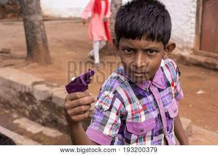 Mysore India - October 27 2013: Closeup of preteen boy looks threatening and pretends to kill with his purple toy gun in Mellahalli hamlet.