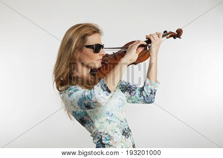 Young blond woman posing in studio with white background. He is a violinist