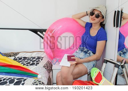 Happy young woman in colorful summer outfit sitting near the red staffed suitcase smiling. Beautiful girl with a Red suitcase loves to travel