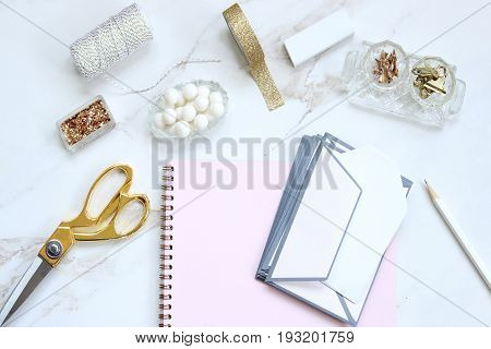 Chic white, pink and gold office supplies on styled desktop. Copy space.