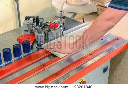At a furniture factory edge plastic roll is fed into an edge banding machine.