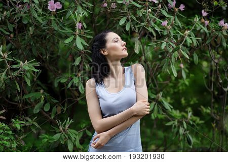 Portrait of beautiful woman in green leaves and blooming flowers. Shallow depth of field