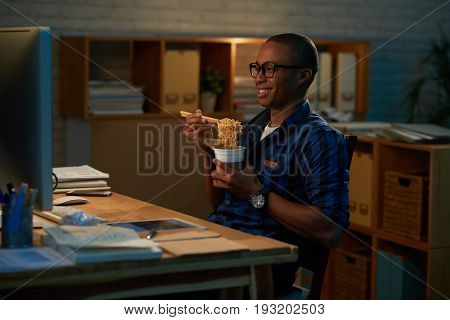 Joyful young businessman watching movie on computer and eating Chinese foot while sitting alone in open plan office late at night