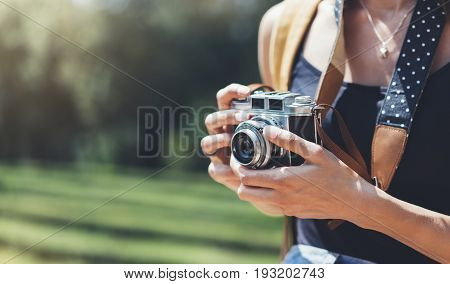 Hipster girl with backpack using vintage photo camera close up copy space of blank empty mockup view tourist holding in hands and photograph on device travel on background Barcelona park sun flare