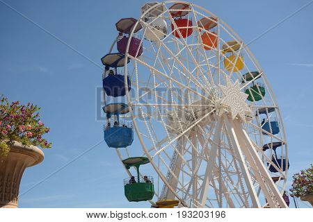 Ferris wheel on the blue sky background. Interesting attraction
