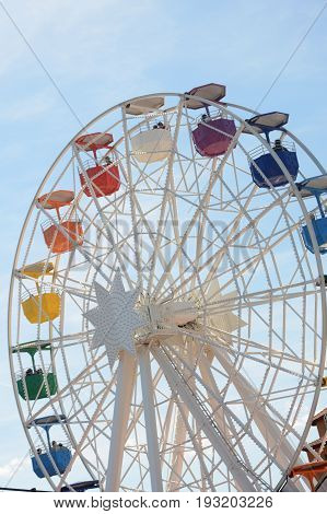 Ferris wheel against the blue sky. Interesting attraction