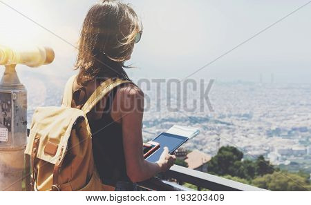 Hipster girl with backpack holding gadget in observation view. Tourist traveler on background panoramic city Barcelona female hands using tablet and map operated binoculars wich sun flare mockup