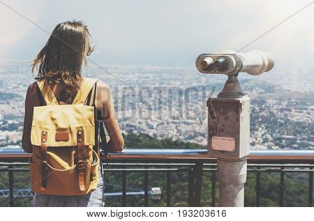 Hipster young girl with bright backpack looking on observation deck and travel plan. Tourist traveler background panoramic view of city coin binoculars. Mock up for text message. Barcelona Tibidabo