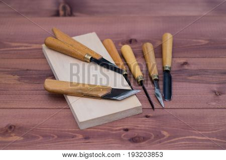Tool kit for woodcarving. Knives for carving on wooden background.
